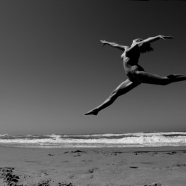 naked woman jumping on the beach