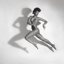 naked brunette jumping in the air with shadow