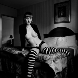 woman with bare breasts and striped socks sitting on a bed