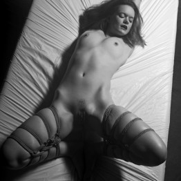 bdsm picture of naked woman tied with rope lying on bed